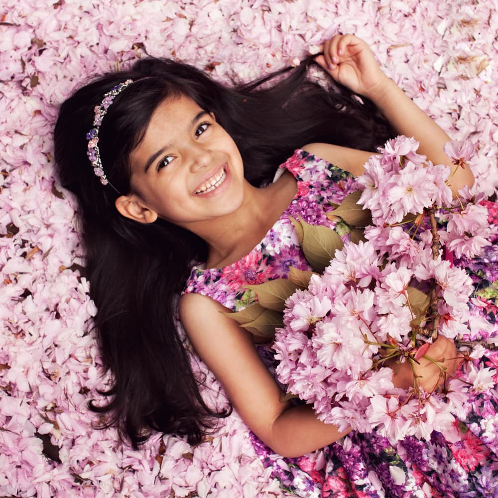 a young lady in a floral dress smiling in the pink blossom