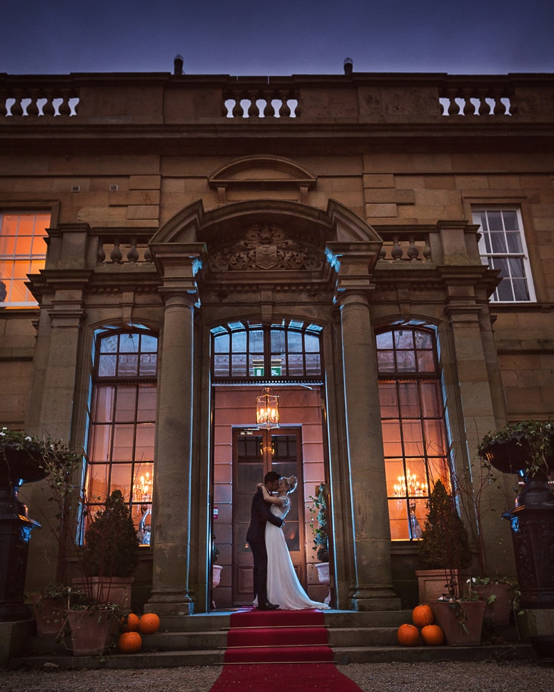 bride and groom embrace at the entrance of Rudby Hall colour image taken at dusk